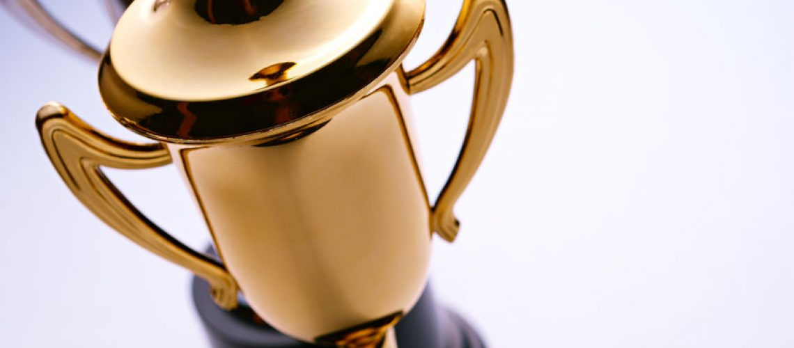 Close up high angle view of a shiny gold trophy award to be awarded to the winner or champion in a competition, with copyspace to the right